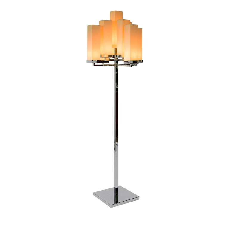 Playing with geometry, the Jaipur floor lamp is a chic and original design from Tura. On a reflective nickel base and stem, the floor lamp is topped with rectangular fabric shades that emit a warm glow. Thanks to its original shape, the lamp is