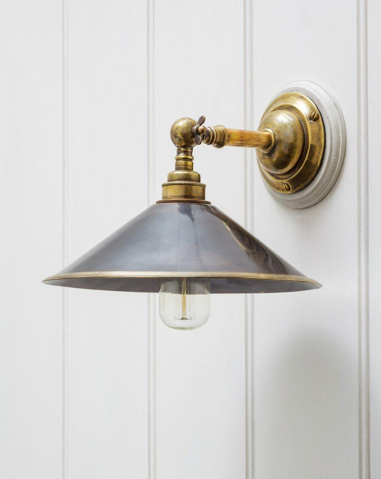 A swivel wall lamp with ringed collared shaft protruding from a rounded base. The reeded metal shade attached to a ball shaped gimbal with locking tap.   Please note the fixture is shown in a number of alternative finishes. Please ask about these