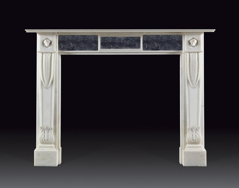 This elegant English Regency style chimneypiece exhibits all the best elements of the period. Carved from statuary marble, the tapered, panelled jambs are wrapped with lotus leaf clasps at the top and carved acanthus at the base, headed by corner
