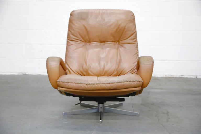 A rare and incredibly laid-back comfortable De Sede S 231 James Bond high-back swivel lounge armchair in an attractive lightly distressed tan leather with thick leather stitching similar to a baseball glove, designed and produced in the 1960s in
