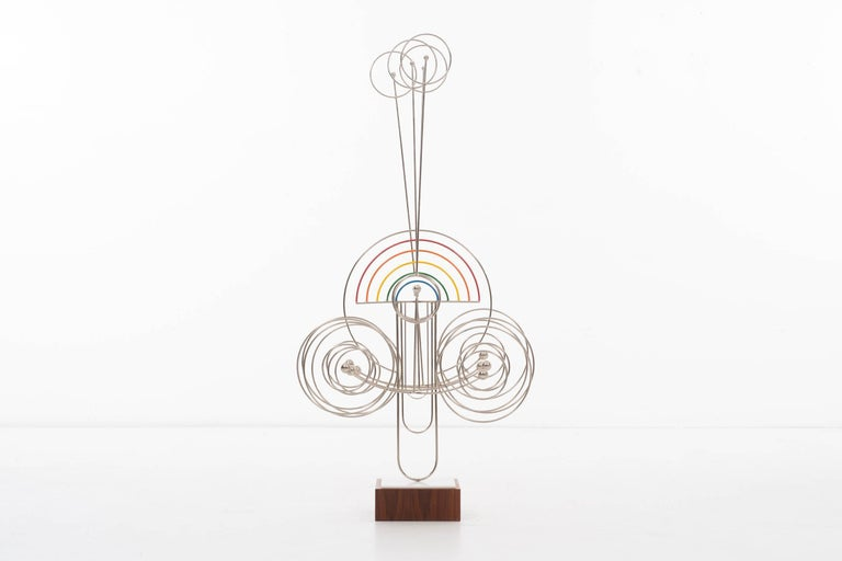 James Burlini sculpture, 4 vertical elements counter weighted move inside a colorful rainbow cradle.