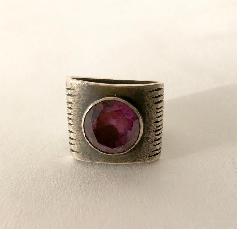 Sterling silver with faceted amethyst stone created by James Parker of San Diego, California.  Ring is a finger size 8 to 8.75 due to its U shaped shank.  In very good vintage condition.  Suitable for a man or woman.