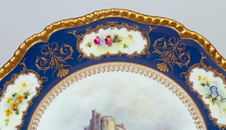 A stunning Royal Worcester porcelain cabinet plate hand painted with a scene titled Castle of Doune by James Stinton and dated 1933. The plate has a central scene of the castle set in a landscape within a decorative border with small floral