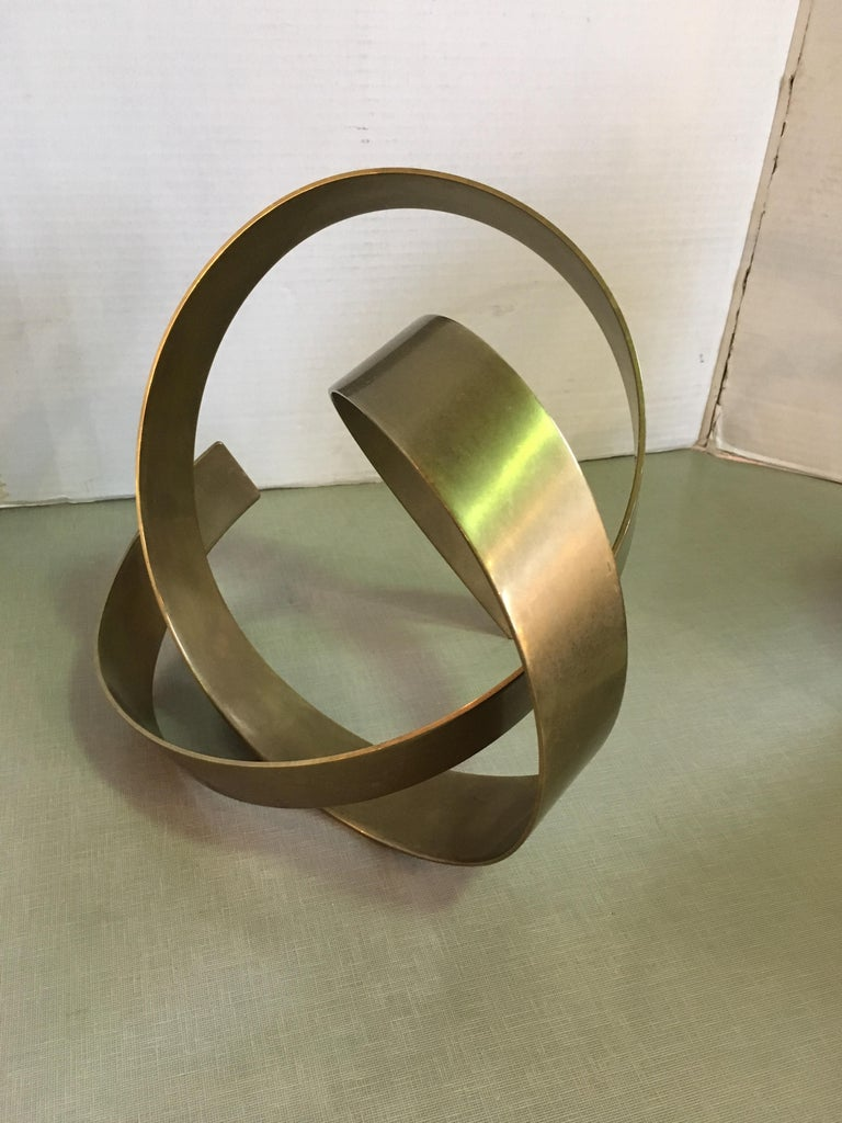 This is a heavy brass abstract sculpture signed and dated by James W. Uhrig.