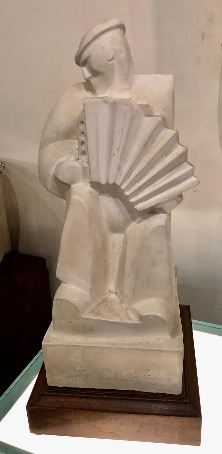 "Jan and Joel Martel ""L'Accordioniste"" The Accordion Player. in cast stone sculpture with painted wood base France, circa 1925. One of the most important sculpture by these brothers, it was done it many different materials, bronze, wood, cast stone."