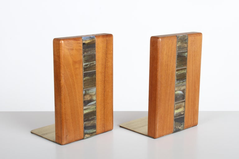Pair of walnut bookends with inset tiles by Jane and Gordon Martz for Marshall Studios on brass bases. Model number WBER5-132. Very nice original condition, small water spot to one bookend top.