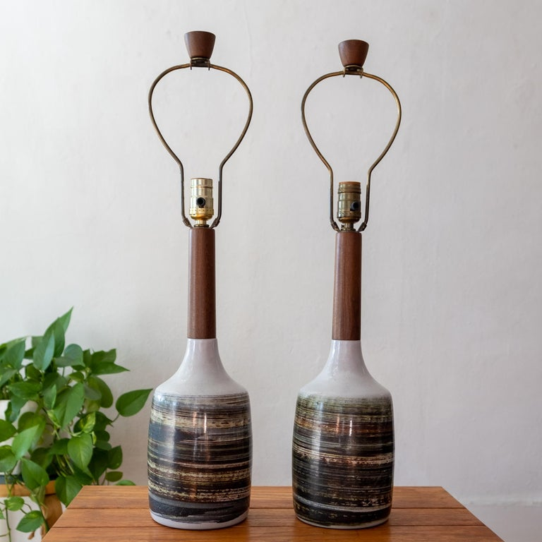 A pair of ceramic and turned walnut lamps by Jane and Gordon Martz for their company, Marshall Studios. Natural tan clay, brushed linear glaze design around the entire base. Includes original harps and finials. Signed.