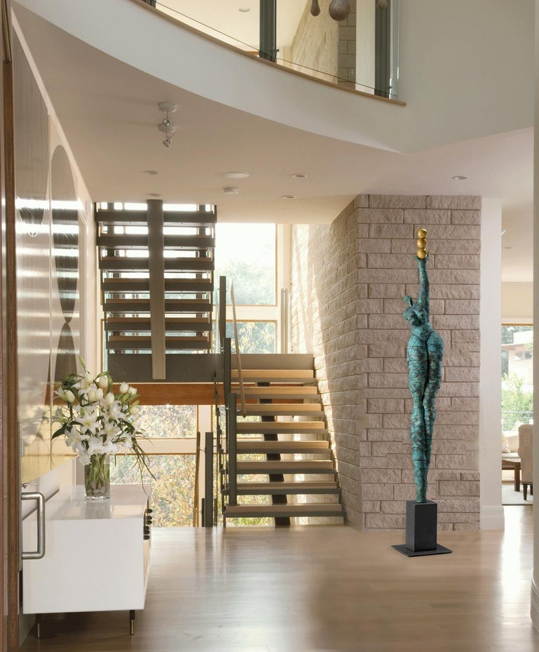 A larger than life figurative sculpture by Jane Burton. This one of a kind piece is well suited for a contemporary interior. When viewed up close, one can appreciate the handwritten script incorporated into the overall blue patina, with soft gold