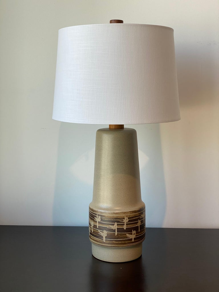 A table lamp designed by husband and wife duo Jane & Gordon Martz. Produced by Marshall Studios, Indianapolis.   Bases are slip-cast and then dipped into glaze and hand painted. Design also incorporates exquisite walnut necks and finials. Bases