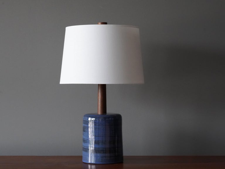 A table lamp designed by husband and wife duo Jane & Gordon Martz. Produced by Marshall Studios, Indianapolis.   The blue base is slip-cast and then dipped into glaze and hand painted. Design also incorporates exquisite walnut neck and finial.