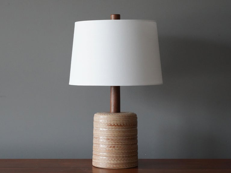 A table lamp designed by husband and wife duo Jane & Gordon Martz. Produced by Marshall Studios, Indianapolis.   The base is slip-cast and then dipped into glaze and hand painted. Design also incorporates exquisite walnut neck and finial. Base is