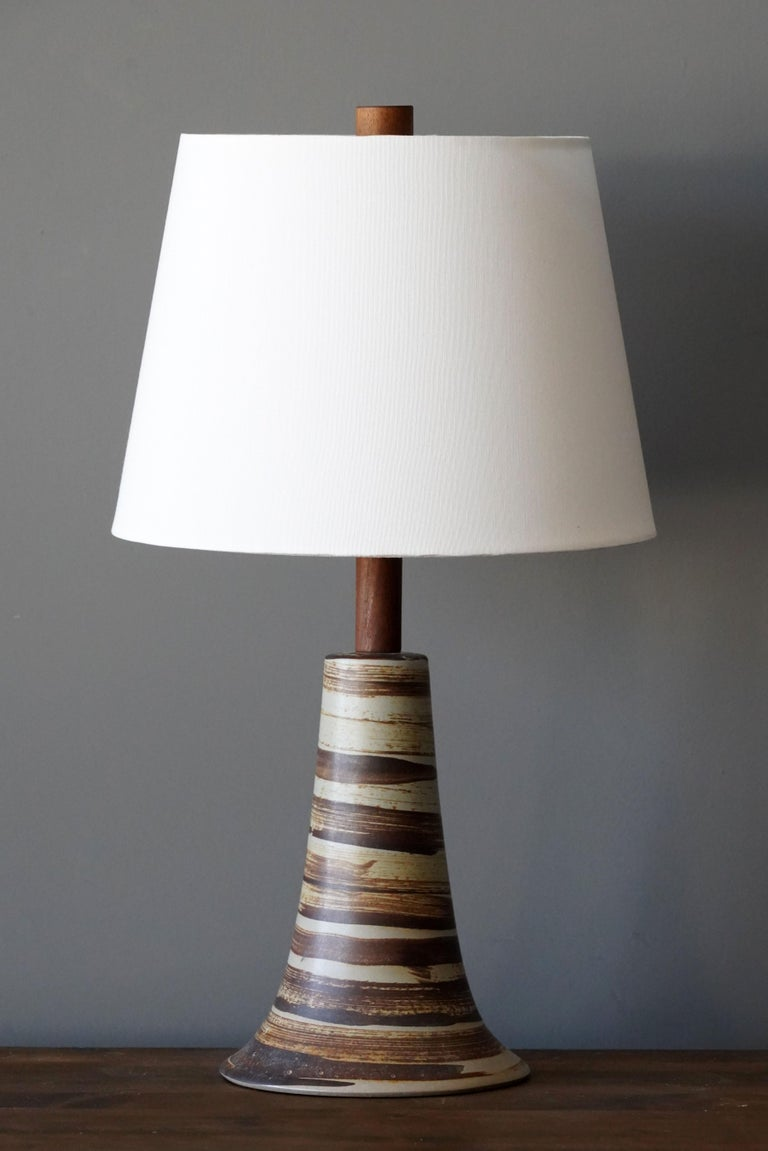 A table lamp designed by husband and wife duo Jane & Gordon Martz. Produced by Marshall Studios, Indianapolis.   Bases are slip-cast and then dipped into glaze. Design also incorporates exquisite walnut necks and finials. Base is signed.   Sold