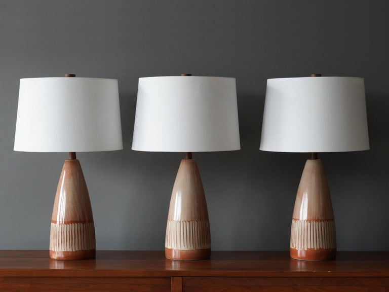 A pair of table lamps designed by husband and wife duo Jane & Gordon Martz. Produced by Marshall Studios, Indianapolis.   The bases are slip-cast and then dipped into glaze and hand painted. Design also incorporates exquisite walnut necks and