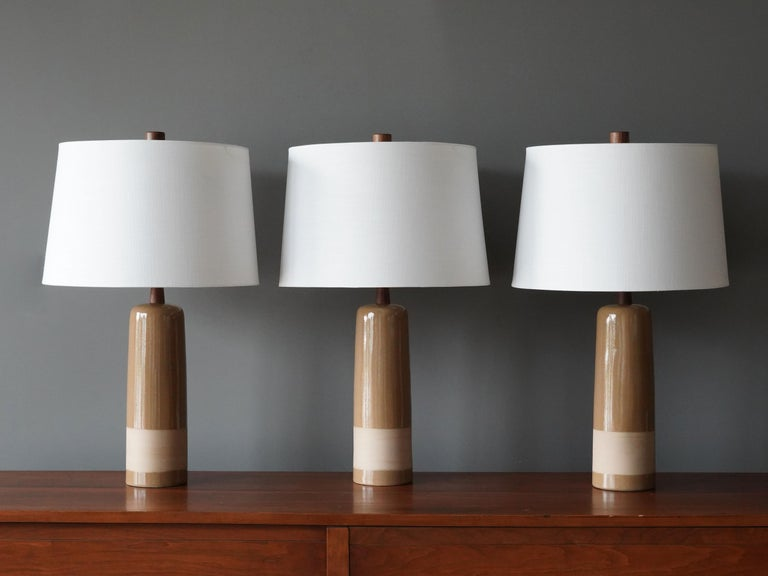 Table lamps designed by husband and wife duo Jane & Gordon Martz. Produced by Marshall Studios, Indianapolis.   The bases are slip-cast and then dipped into glaze and hand painted. Design also incorporates exquisite walnut necks and finials. Bases