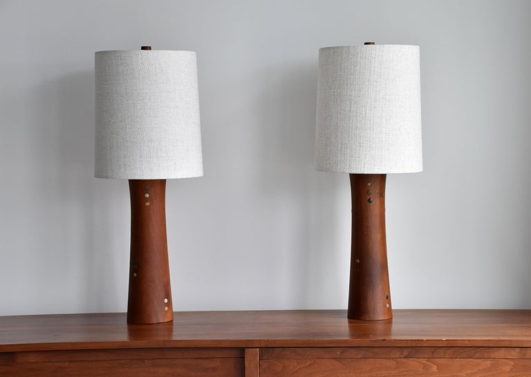 A pair of table lamps designed by husband and wife duo Jane & Gordon Martz. Produced by Marshall Studios, Veedersburg, Indiana.   Bases are sculpted walnut, with ceramic inlays.   Jane & Gordon Martz works are represented in the permanent