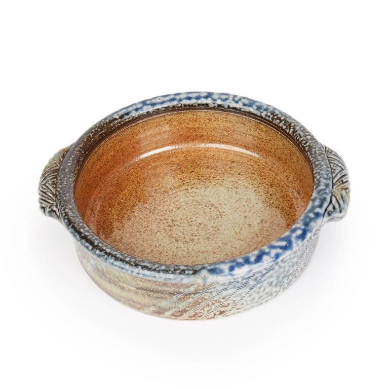 A stylish vintage British studio pottery twin handled bowl by renowned potter Jane Hamlyn and made at Millfield Pottery near Doncaster. The rounded stoneware bowl has impressed wheel markings and circular markings with moulded patterned handles to