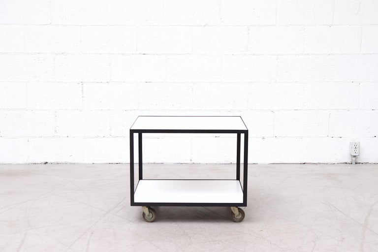 Janni Van Pelt style rolling bar cart with black enameled metal frame and inset white formica surfaces. In original condition with visible wear and some enamel loss.