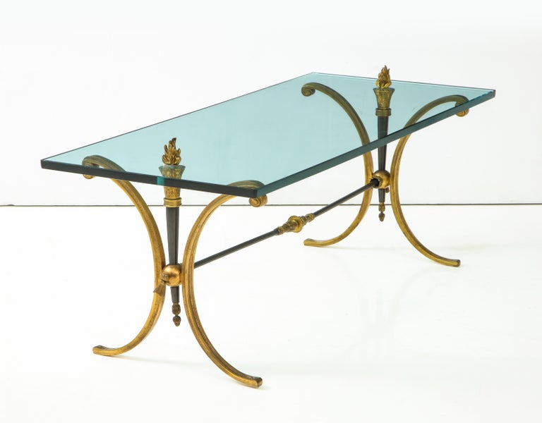 Jansen Empire style bronze coffee table having glass top with flame finial decoration supported on downswept legs and cross stretcher.