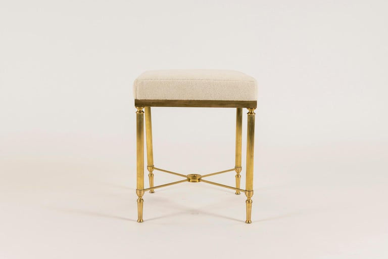 A beautifully constructed vintage neoclassical style detailed brass bench with tapered and fluted legs and radiuses stretchers in the style of Maison Jansen. Seat is upholstered in a creamy Pollack Luxe Alapaca Fleece. Also available C.O.M.
