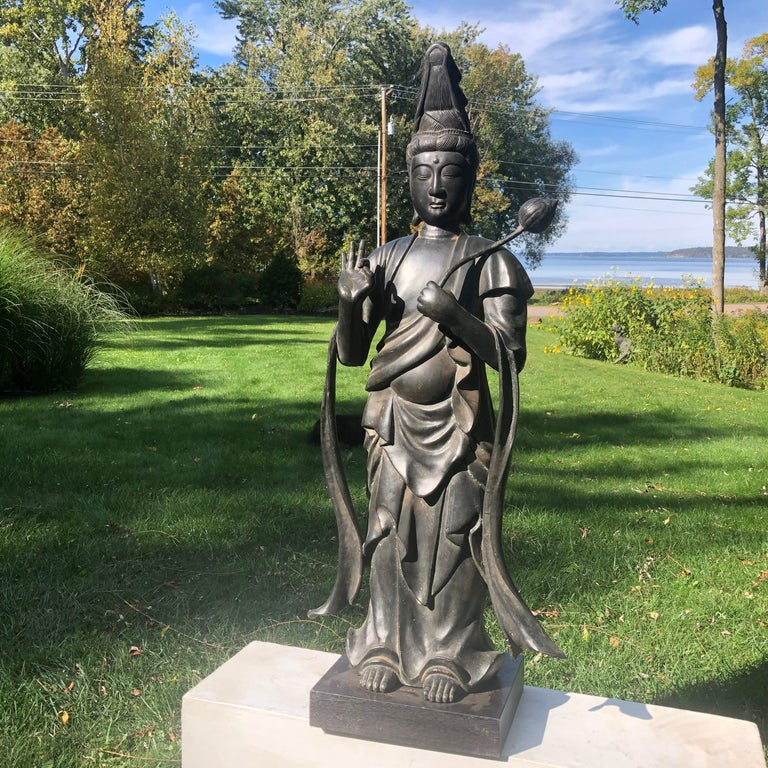 Good Garden or Indoor Choice- Ex Christie's Auction.  Japan, an elegant and finely cast antique bronze standing Kanon Maitreya or Guan Yin clutching a lotus branch - a sign of purity- and with lovely pensive down cast facial expression and eyes, a