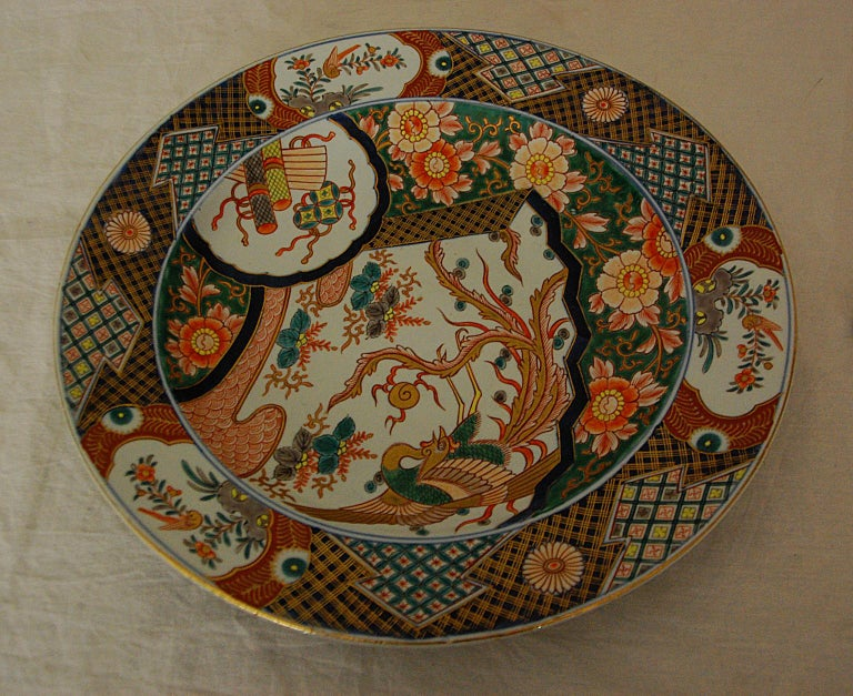 Japanese Imari charger of large and impressive size being 15 13/4 inch in diameter. The decoration is hand painted in underglaze blue and overglaze enamels, highlighted by gold leaf detailing. The central motif is a phoenix rising into the air,