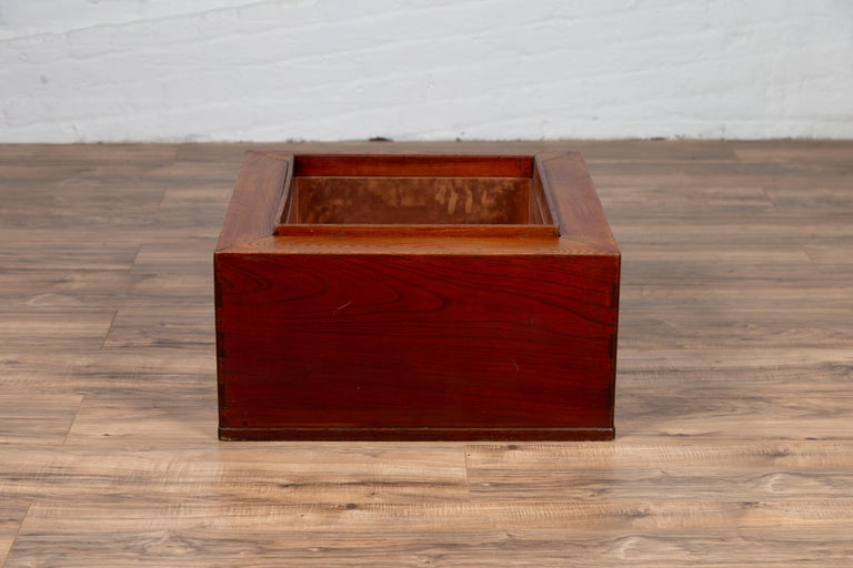 A Japanese rectangular keyaki wood hibachi from the 19th century, with copper liner. Used for cooking or warming sake or tea, this elegant Japanese 19th century hibachi features a rectangular frame surrounding the central opening lined with copper.
