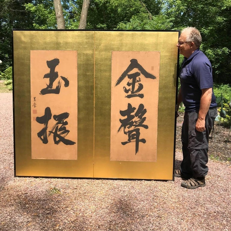 Japan, a fine two-panel screen Byobu of broad black brush strokes on gold ground, in big bold calligraphy roughly translating as