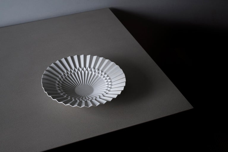 This tray is designed by Denis Guidone and handmade in Japan by Risogama for Hands on Design, a traditional pottery. It reminds the Japanese tradition of Origami, the designer uses the white Arita porcelain like paper and lighten the appearance of