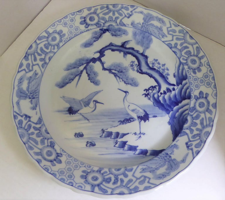 Beautiful Meiji period blue and white Japanese Imari Charger depicting a standing crane or stork under a pine tree at water's edge and another coming back for a landing. Two stylized turtles are seen swimming nearby. Rim decorated with 3 medallions