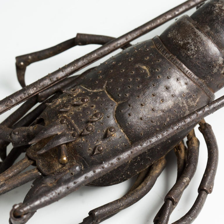 This articulated okimono represents a naturalistically rendered lobster, with fully articulated limbs, antennae, body, and tail and comes with an inscribed wood storage box.