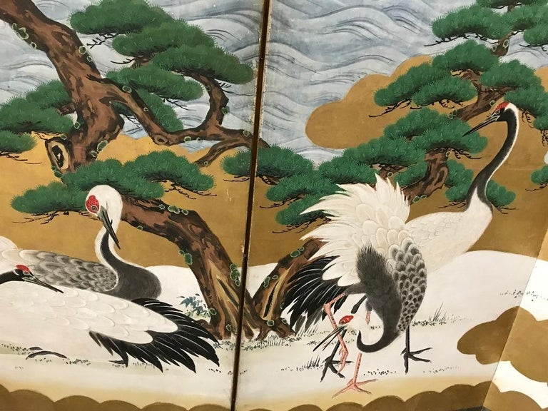 A magnificent six panel Japanese Byobu folding screen (likely Meiji Period but possibly Edo period) depicting cranes at play near the ocean shoreline. Crashing waves and large juniper trees give the image a rather unique feel. The colors and gold