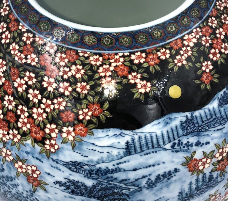 Mesmerizing Japanese contemporary decorative porcelain vase, painstakingly intricately hand painted in black, blue and red Set against a stunning globular background in black , a signed masterpiece by second-generation master porcelain artist of the