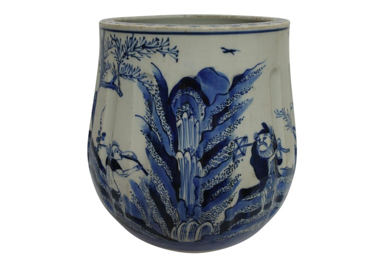 A 19th century hand-painted blue on white Japanese porcelain vase in the Chinese style, having a fluted body, and decorated with figures in a nature landscape on the front, and writing on the backside.