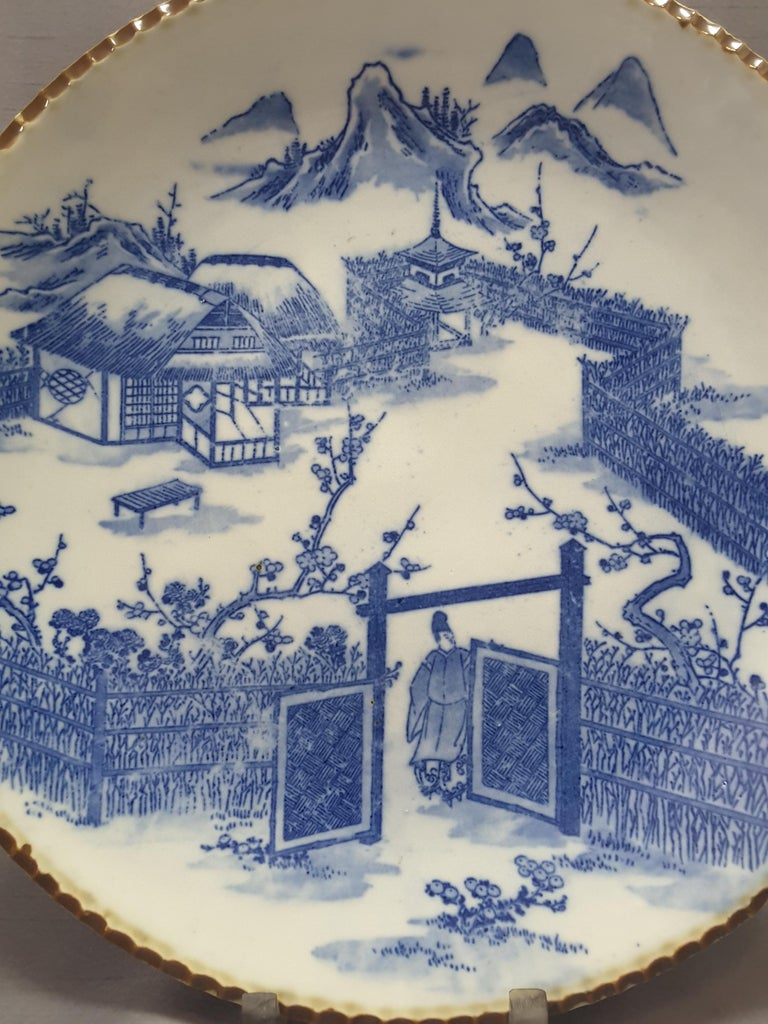 Japanese Blue & White Charger, Compound/Home Scene, Late 19th/Early 20th Century. Scalloped edge with rust brown detail, bright blue on white decoration.The back has double blue ring detail, spur firing from kiln, three scene decoration on back rim.