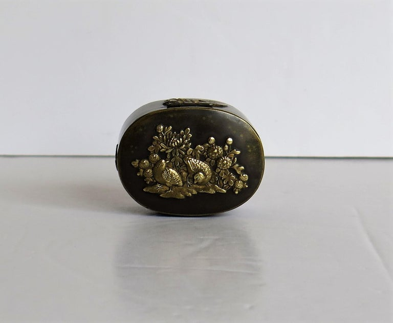 This is a small Japanese bronze and brass rectangular box with a snap top hinged lid and detailed embossed applied patterns of birds, flowers and butterflies all dating to the 19th century Meiji period.
