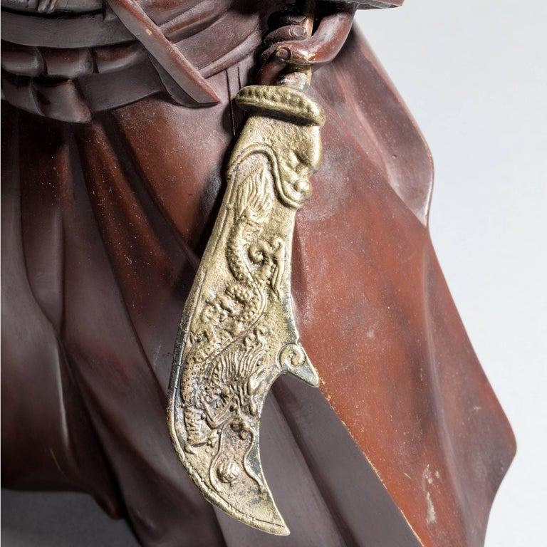 An attractive Japanese bronze of a Samurai with a bisen-to, decorated with a reddish patination, signed, on a wood stand.