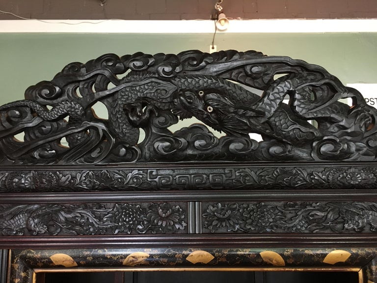 A powerfully carved and ebonized Japanese Meiji Period display cabinet, known as a shodana, made for the Victorian export market.  The cabinet is heavily carved in relief with writhing dragons carved throughout, several featuring mother of pearl