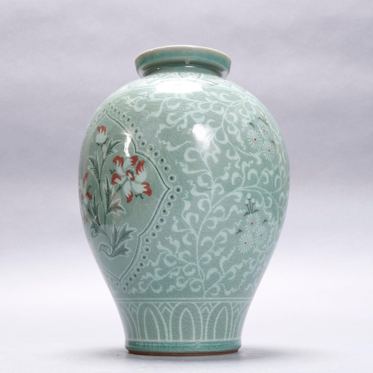 A Japanese bulbous porcelain vase offers jade green Celadon glazing with all-over scroll and foliate decoration having central floral reserve, repeating stylized leaf collar and base rim, chop mark signed on base, 20th century.  ***DELIVERY NOTICE –
