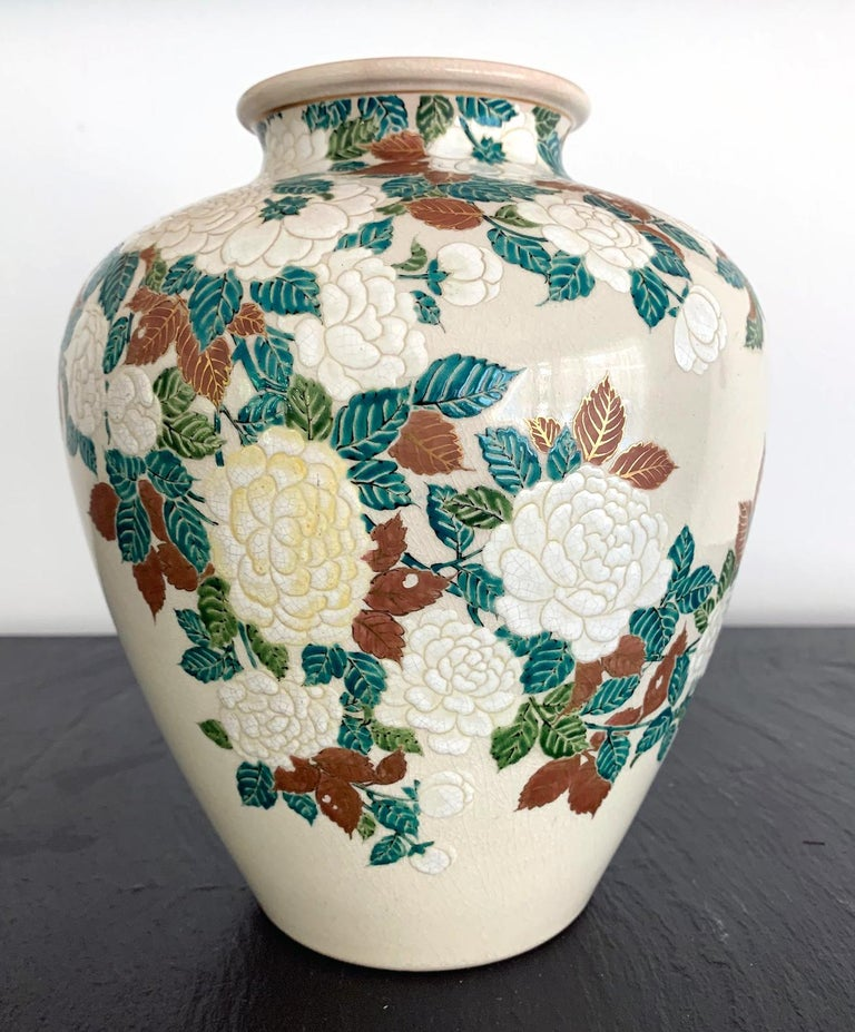 This stoneware vase of a jar form was finely decorated with low relief carving and delicate colored glazes depicting bundles of peony flowers. It was made by Ito Tozan I (1846-1920) circa 1890-1900s in the late Meiji Period. The color pallet was