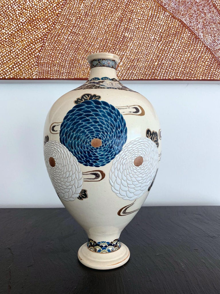 A ceramic vase in an elegant form and fine over glaze decoration. Japanese Satsuma ware that was likely made in Kyoto circa late 19th century. The vase was finely decorated with low relief carving depicting bundles of pompon chrysanthemums in white
