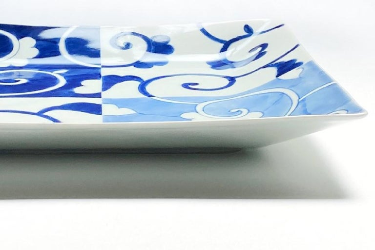 Japanese contemporary porcelain dinner plate in an elegant square shape, hand-painted in blue uderglaze in cobalt and light blue to showcase a graceful arabesque or karakusa pattern. The artist's signature appears on the reverse side. A desert or