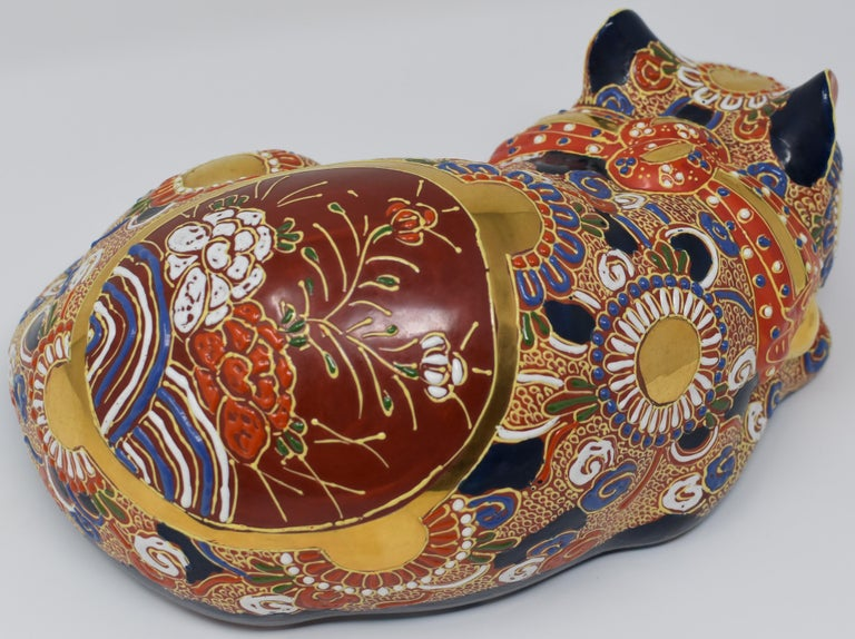 """Unique contemporary Japanese sleeping cat, a gilded and hand-painted porcelain piece from the Kutani region of Japan. The cat is adorned with multiple golden medallions and is covered with raised loops characteristic of the Kutani """"moriage"""""""