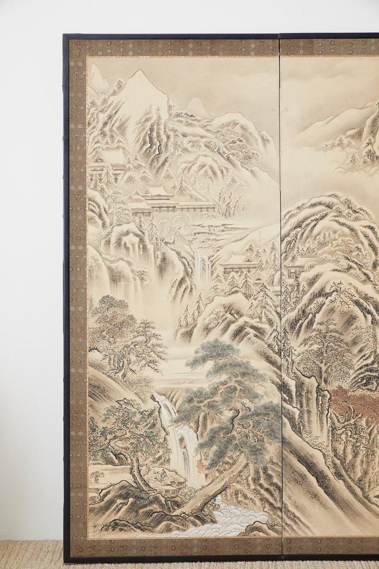 Serene Japanese late Edo period four-panel screen depicting an autumn/winter at the west lake in Hangzhou. Tall, steep mountains border the landscape scene creating an immense sense of space. Ink and color pigments painted on paper in the unkoku