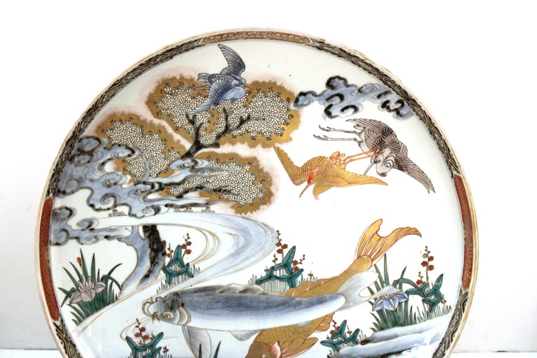 Japanese Meiji period large porcelain charger with fish theme and decorative border. The piece was likely made during the Meiji Period. In great antique condition with age-appropriate wear and use.