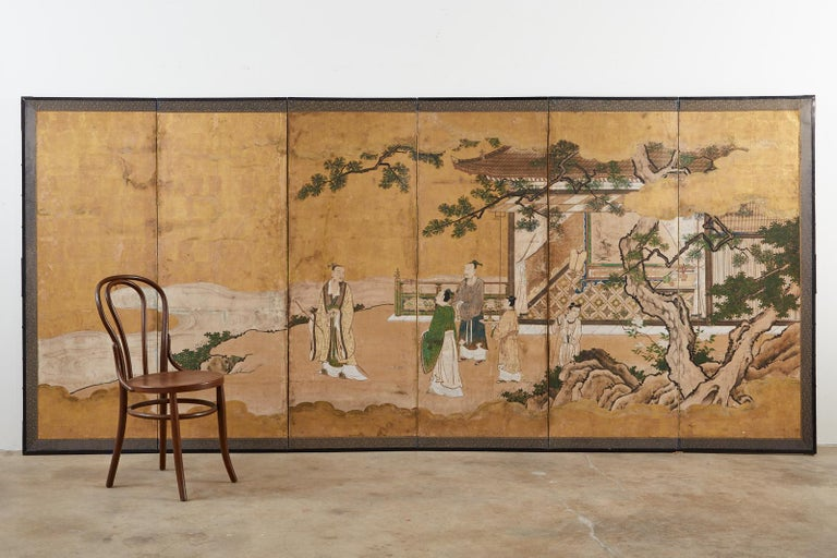 Early 18th century Japanese Tokugawa Edo period six-panel kano screen depicting the Emperor in conversation on a garden terrace. Crafted from ink and natural color pigments on gold leaf squares set in a lacquered frame. The genre is based on the