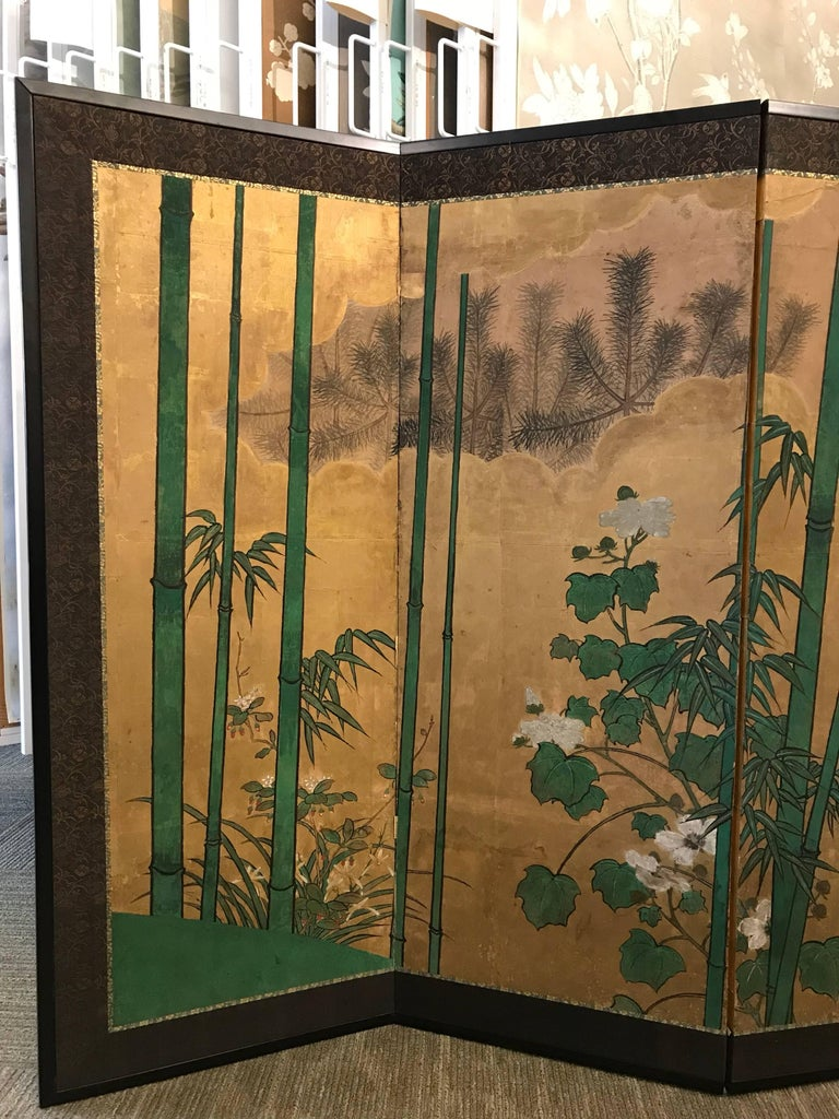 A 19th century eight panel Japanese screen with bamboo, pines, and gold leaf clouds.