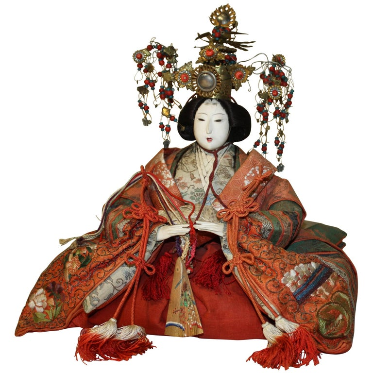 A Meiji Period Japanese doll depicting the Empress with elaborate head-dress, and wearing period clothing, 19th century. The face and hands glazed with crushed oyster shells (Gofun) to create the bright white finish.