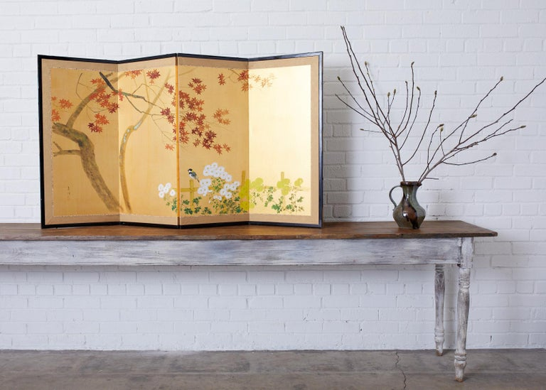 Delightful Japanese Showa period four-panel screen depicting an autumn maple tree over a bamboo fence with flowering chrysanthemums and a small bird. Ink and color pigments painted on radiant gilt colored silk. Made in the Nihonga school style