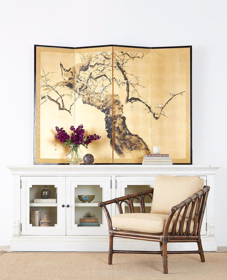 Impressive Japanese four panel screen depicting ancient flowering prunus tree with spring blossoms. Painted with ink and color pigments over gilt squares in the Nihonga school style. Signed by artist Gakusui with a seal on left side. Set in a