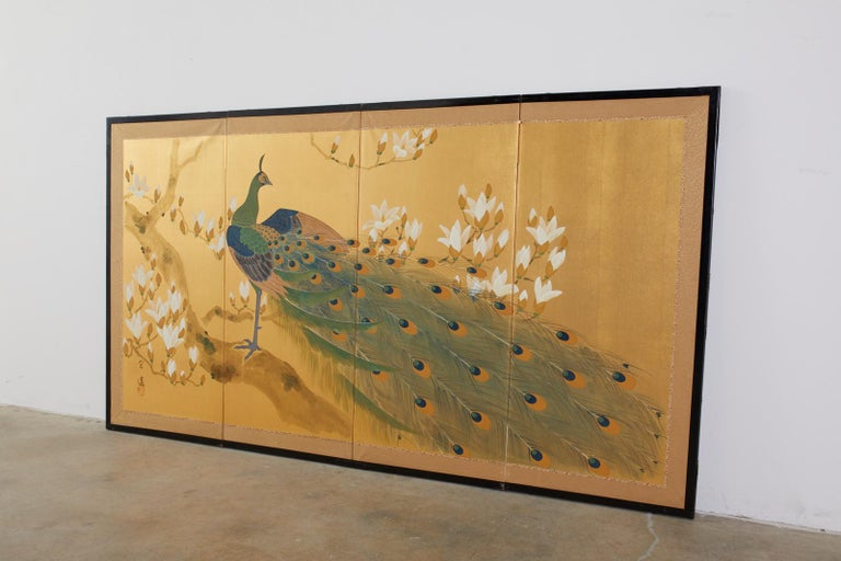 Gorgeous Japanese four-panel byobu screen featuring a peacock perched in a flowering magnolia tree. Made in the Nihonga school style with ink and color pigments on gilt squares. Signed by artist Soen with a seal. Set in a black lacquered wood frame
